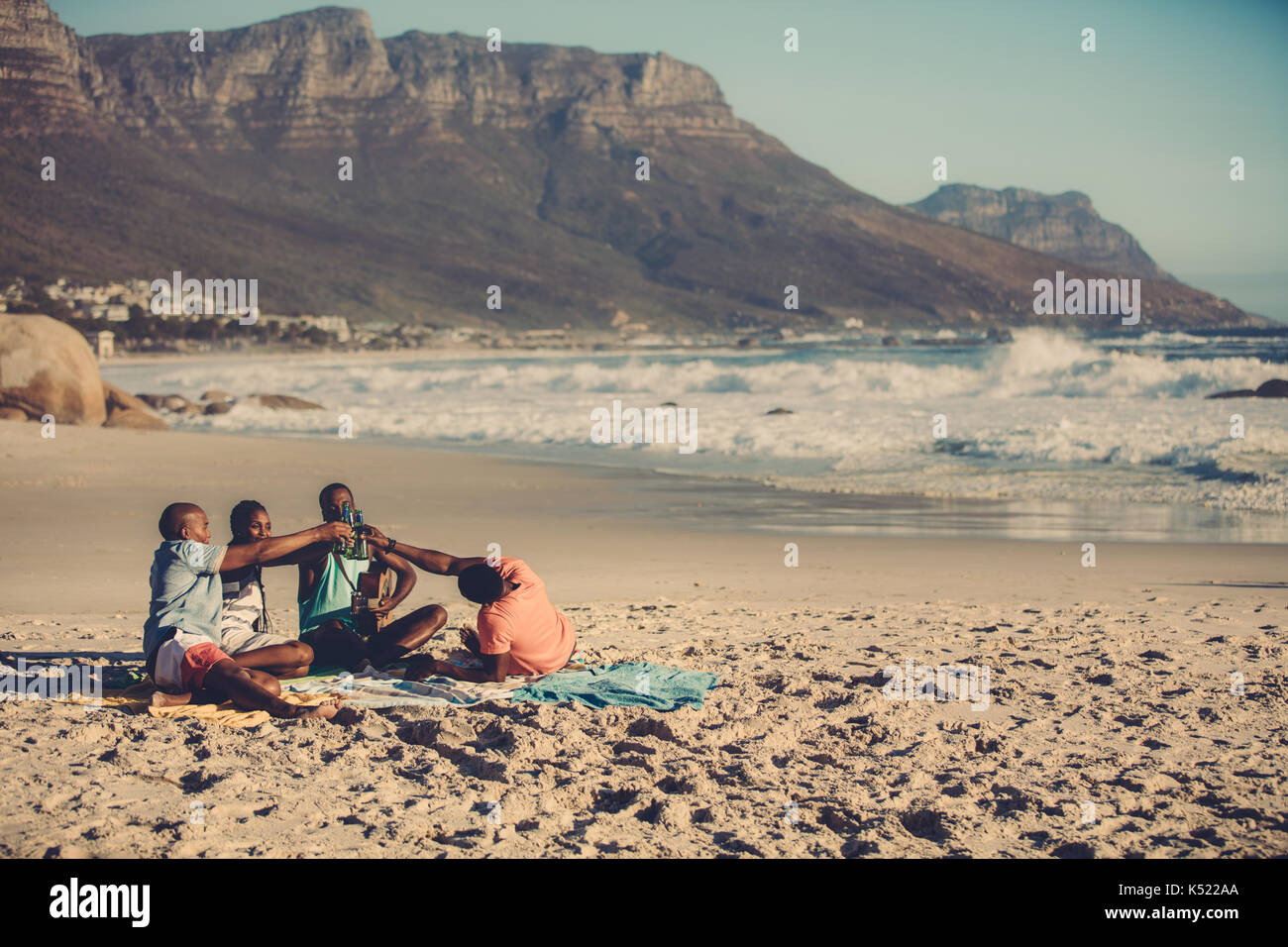 Portrait of group of friends playing guitar and drinking beer. People on the beach having a party. - Stock Image