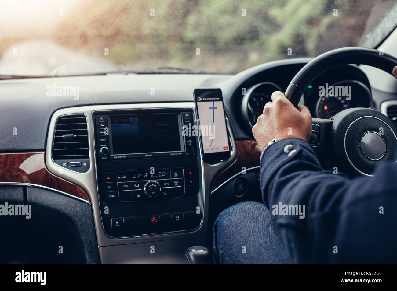 Man driving car with mobile navigation system. Male using mobile phone with map gps navigation in the car. - Stock Image