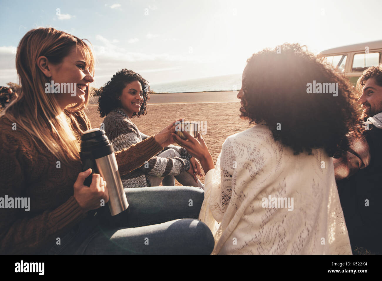 Friends on roadtrip taking a break after traveling. Group of man and women sitting outdoors and drinking coffee. - Stock Image