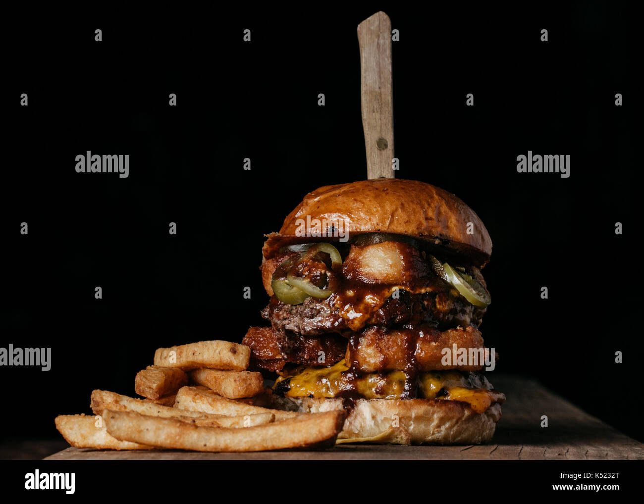 Double Meat Burger with fried onion rings, cheese and pickled jalapeños Stock Photo