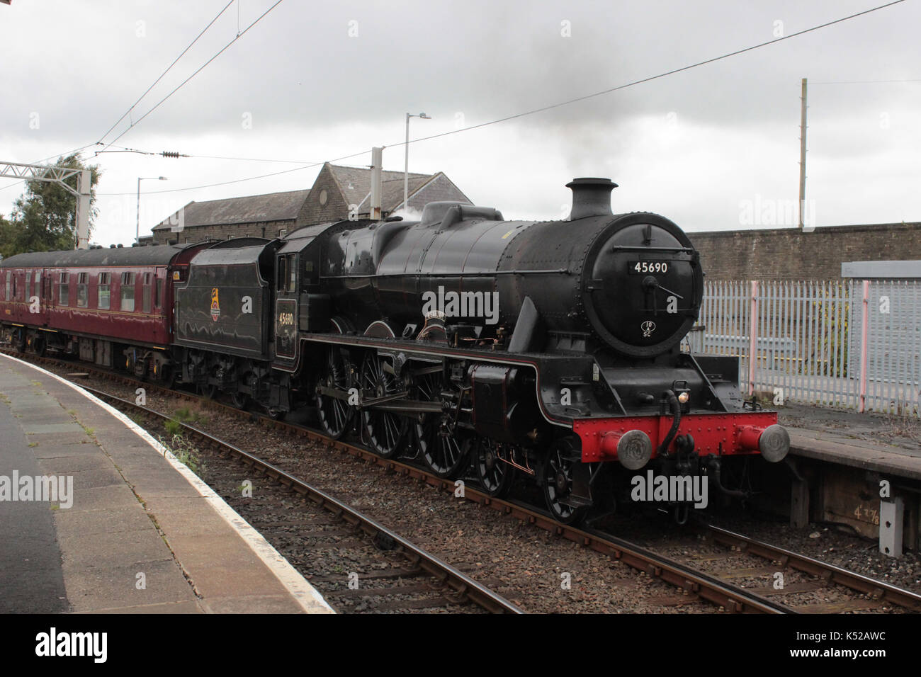 Jubilee class steam locomotive number 45690 named Leander arriving at Carnforth railway station seen entering Platform 1. - Stock Image