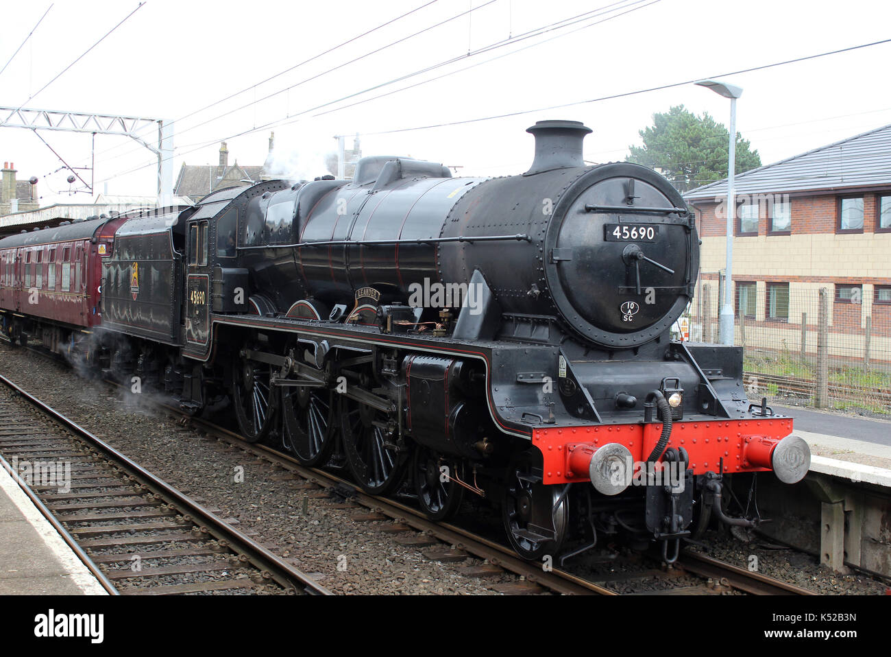 Jubilee class steam locomotive number 45690 named Leander in Carnforth railway station platform 1 alongside the West Coast Main Line. - Stock Image