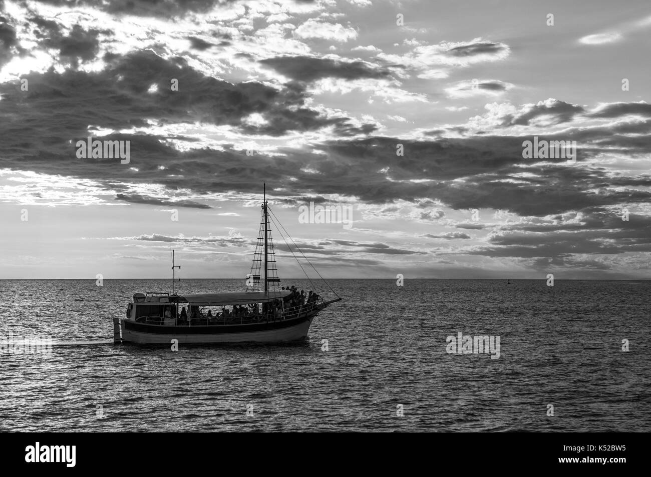 A tourist boat on the sea at sunset (desaturated) - Stock Image