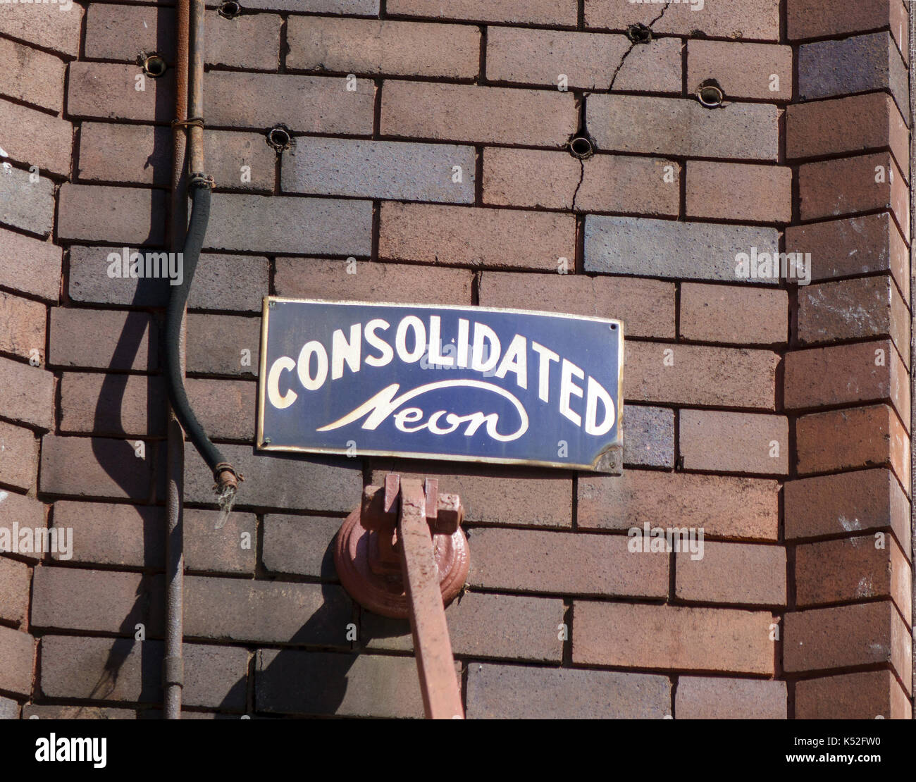 An Old Consolidated Neon Company Sign Sydney Australia Screwed To A Brick Building - Stock Image