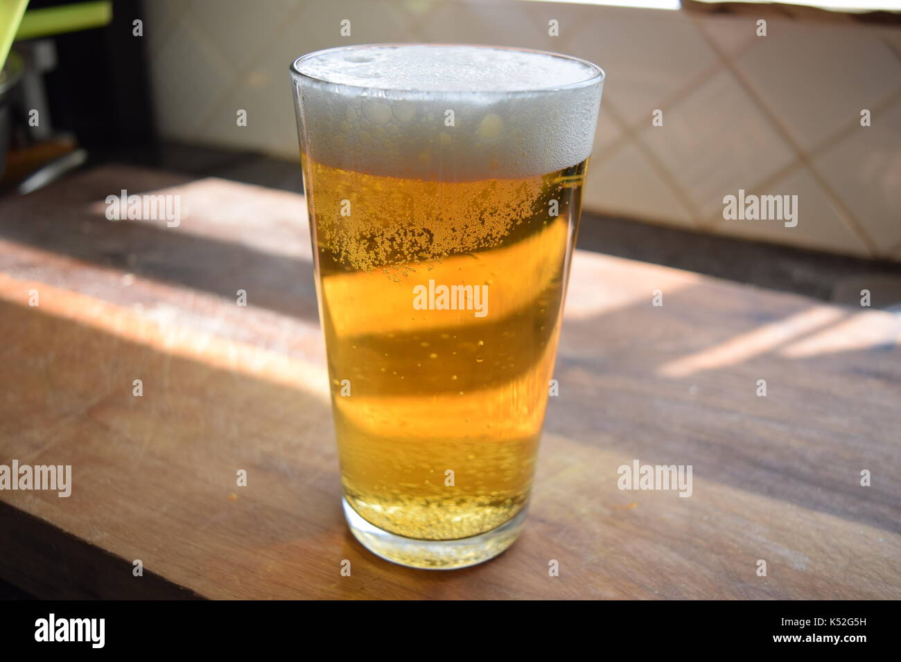 Tall pint of beer on a wooden surface - Stock Image