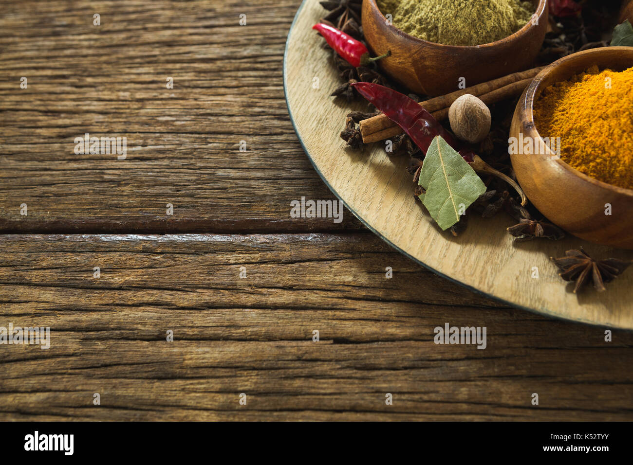 Overhead of various spices arranged in plate - Stock Image