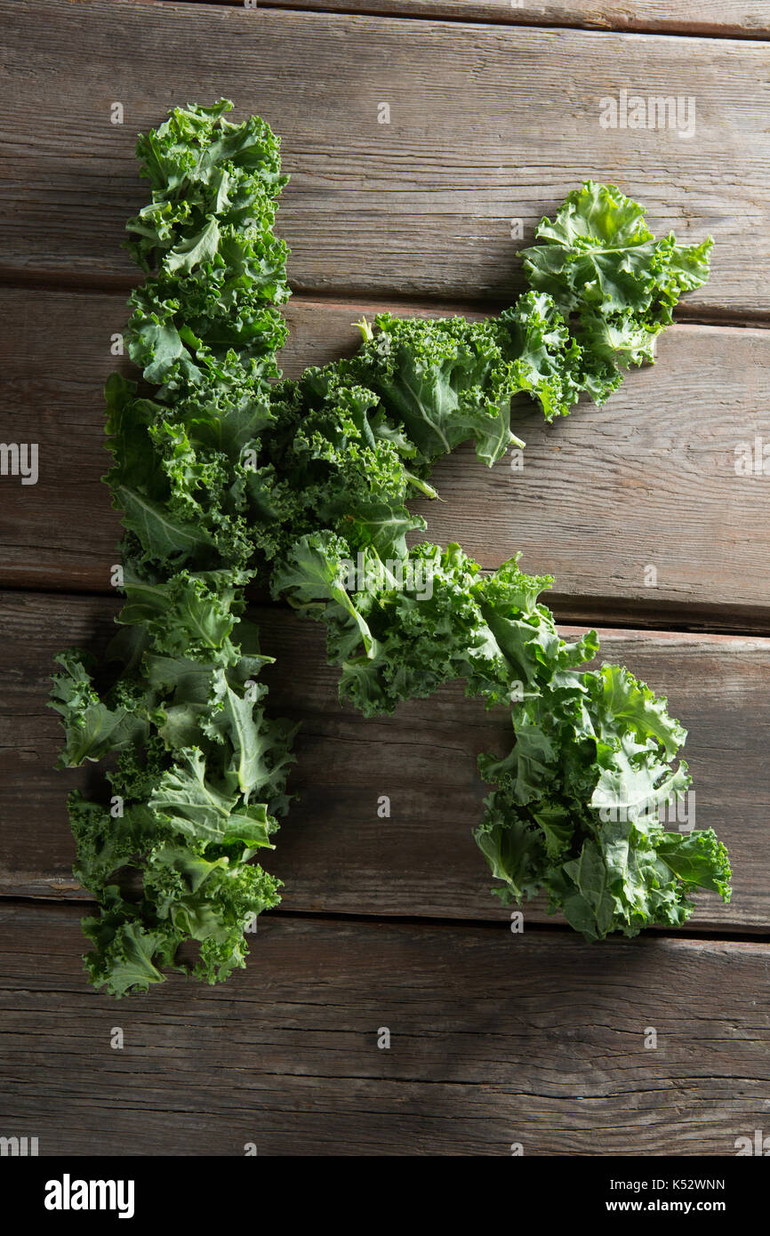 Overhead view of letter K made with fresh kale leaves on wooden table - Stock Image