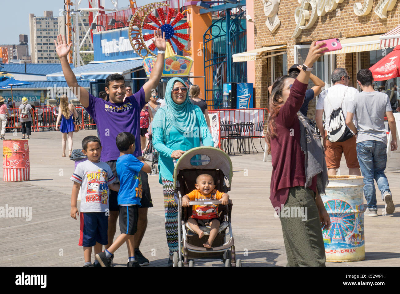 A Muslim family taking a selfie on the boardwalk in Consy Island, Brooklyn, New York City. - Stock Image