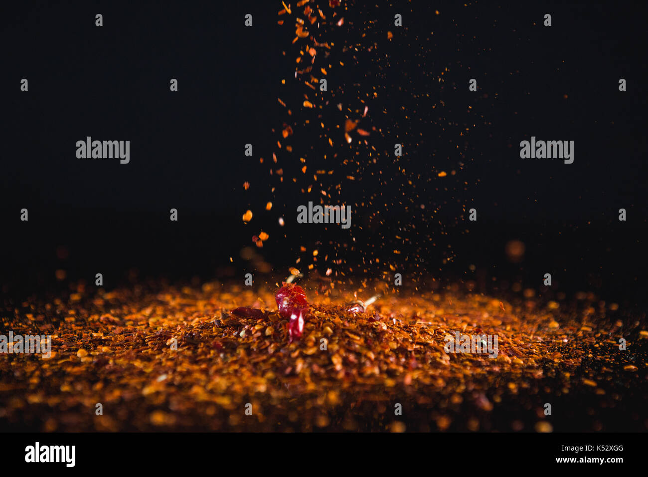 Close-up of red chilli flakes against black background - Stock Image