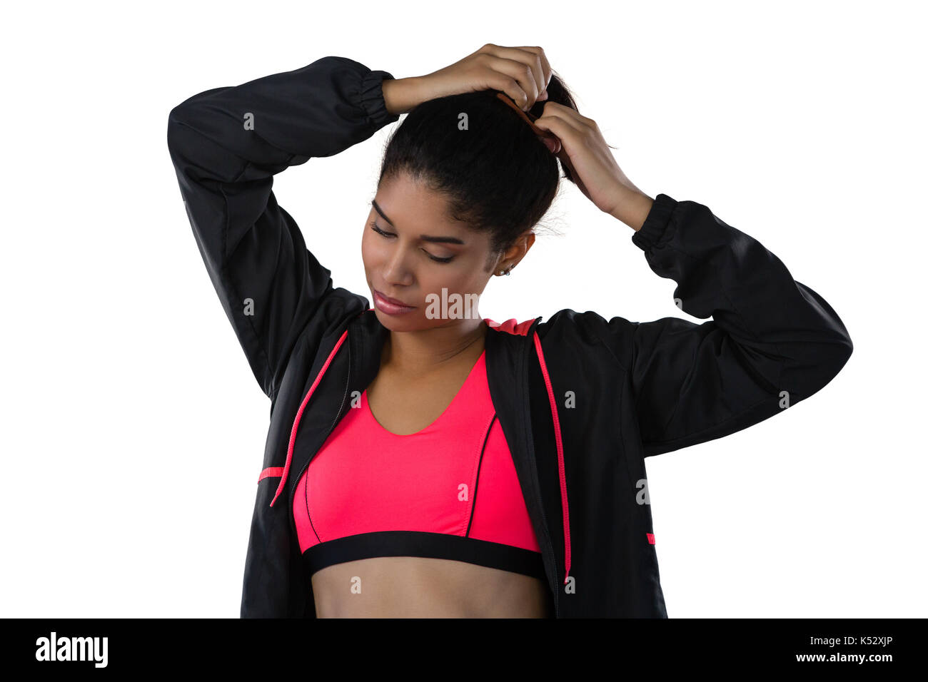 Female athlete tying hair while standing against white background - Stock Image