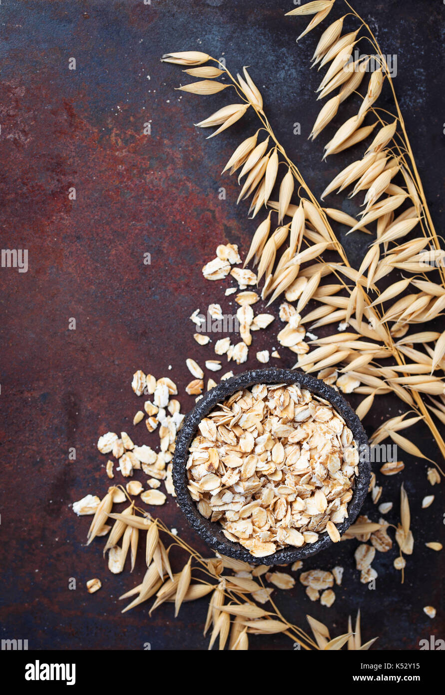Oat flakes and spikelets on rusty background - Stock Image