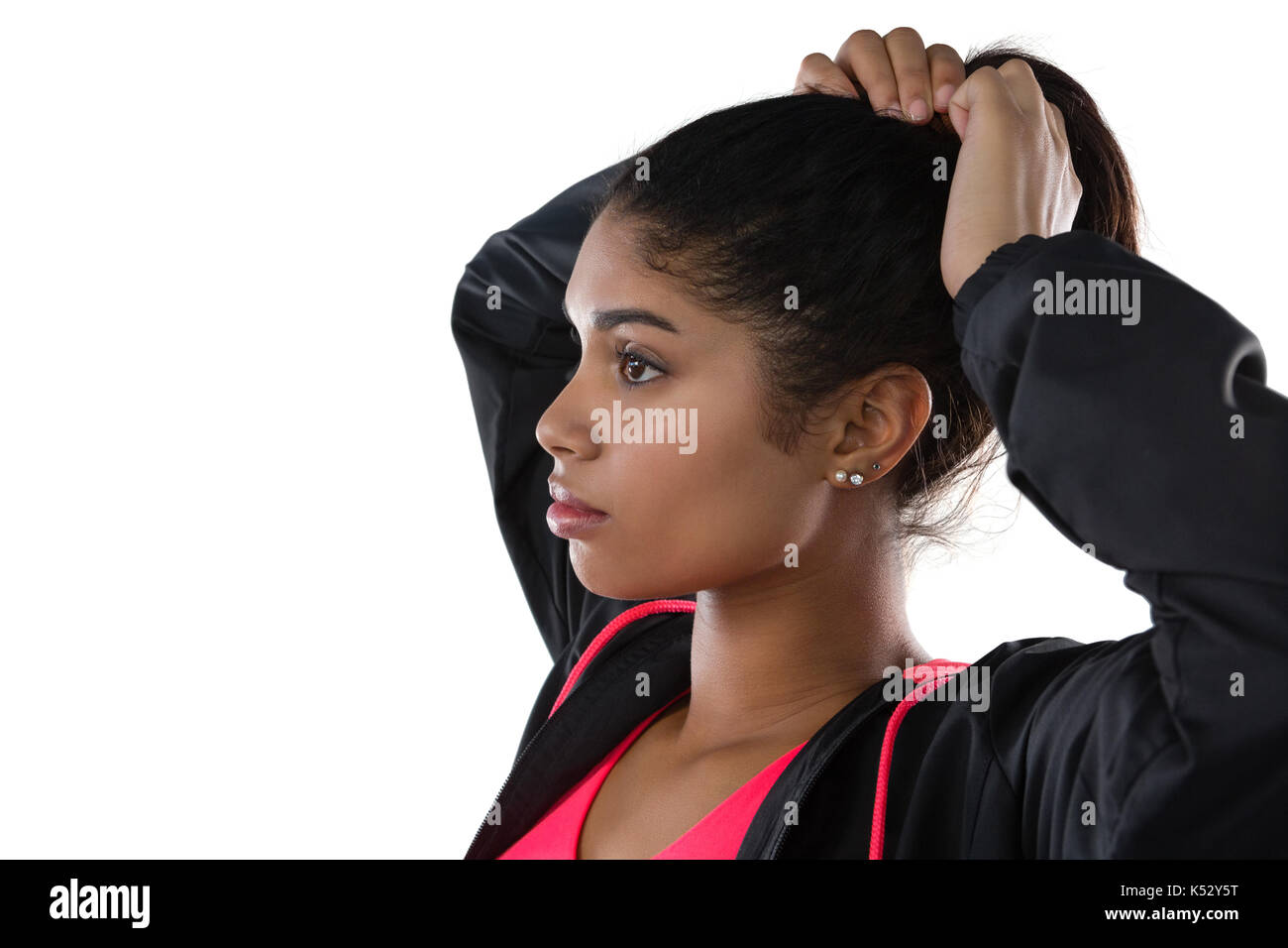 Young female athlete looking away while tying hair against white background - Stock Image