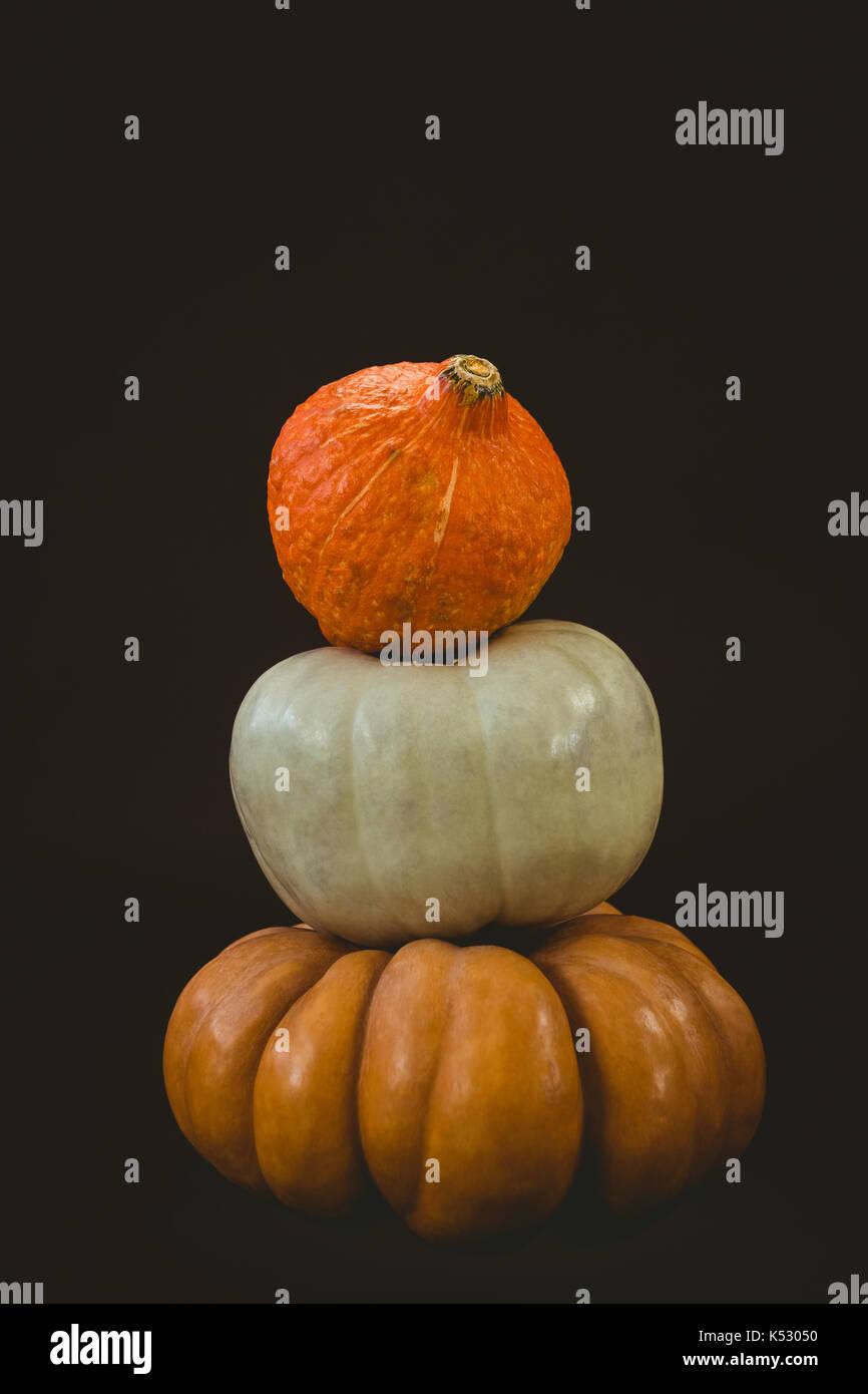 Stack of pumpkins against black background - Stock Image