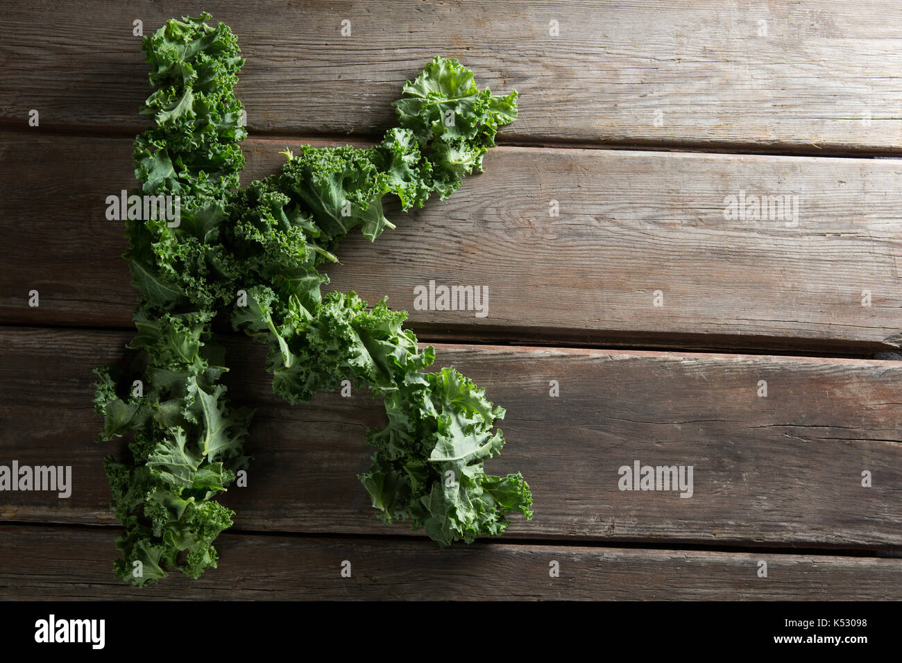 Overhead view of letter K made with kale leaves on wooden table - Stock Image