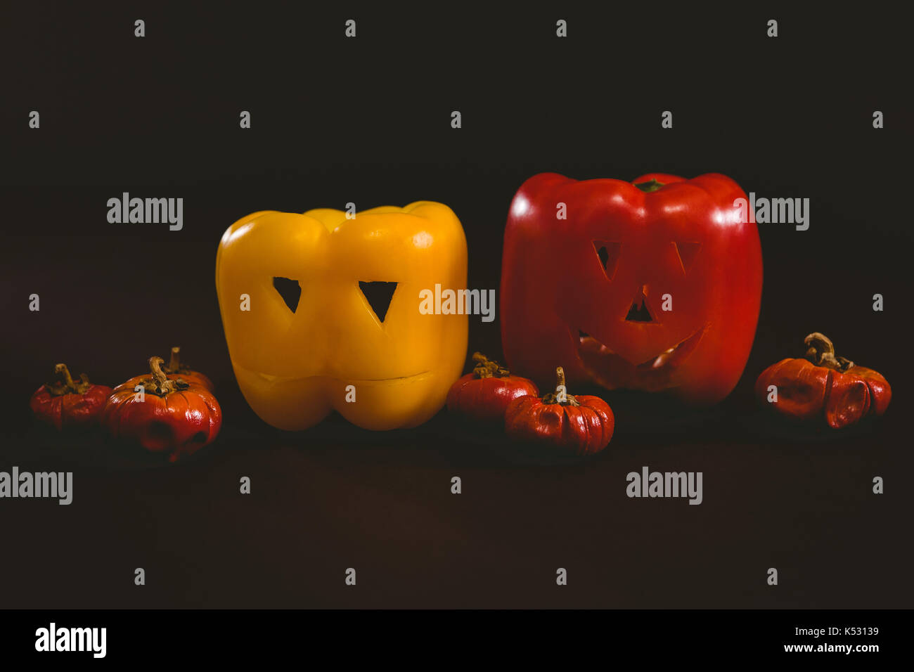 Close up of carved bell peppers with small pumpkins over white background - Stock Image