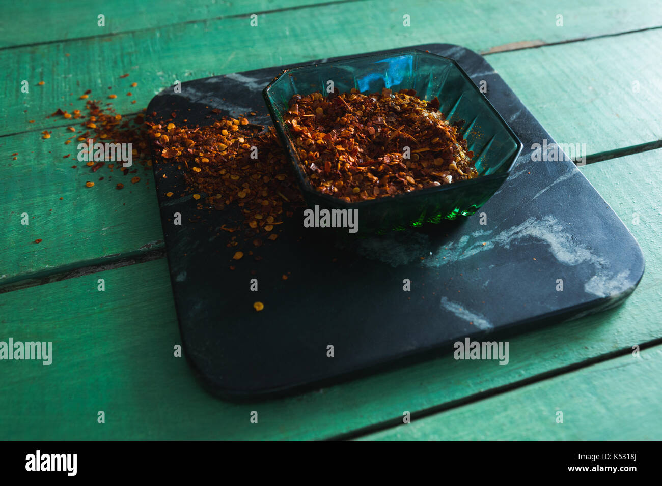 Crushed red pepper in bowl on wooden table Stock Photo
