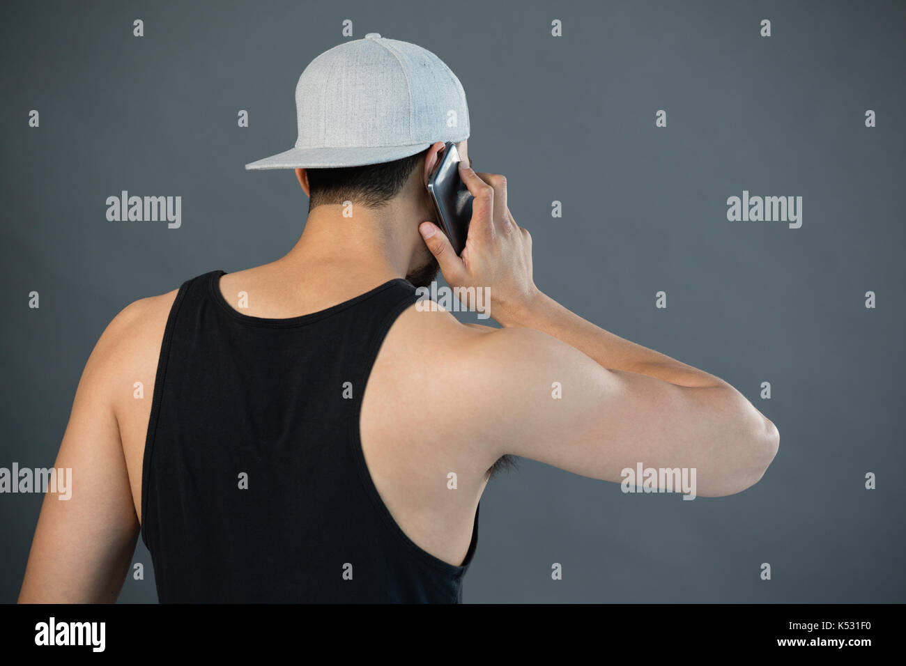 Rear view of man talking on mobile phone against grey background Stock Photo