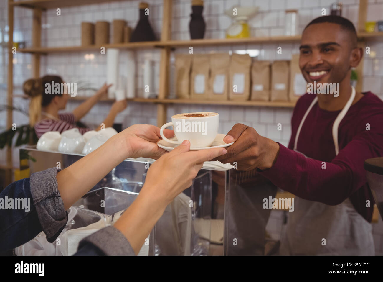 Cropped hands of customer receiving coffee from male owner at cafe - Stock Image