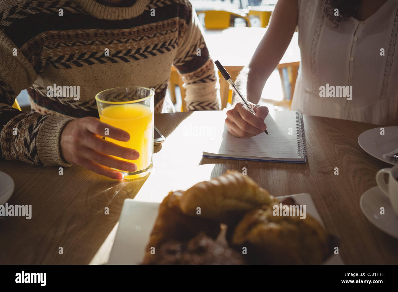 Mid section of woman with man writing on book while sitting at table in cafe - Stock Image