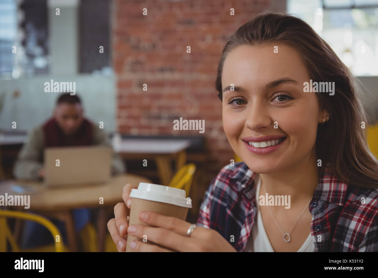 Portrait of happy young woman holding coffee cup at cafe Stock Photo