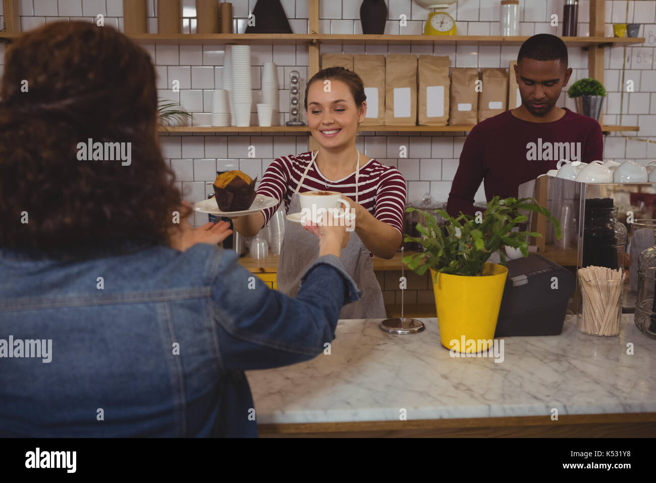 Young female owner serving coffee and muffin to customer at cafe - Stock Image