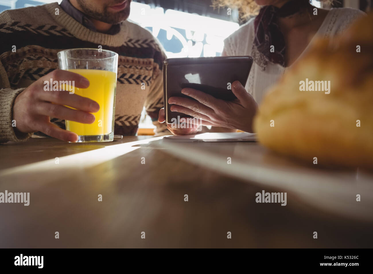 Mid section of woman with man using digital tablet at table in cafe - Stock Image