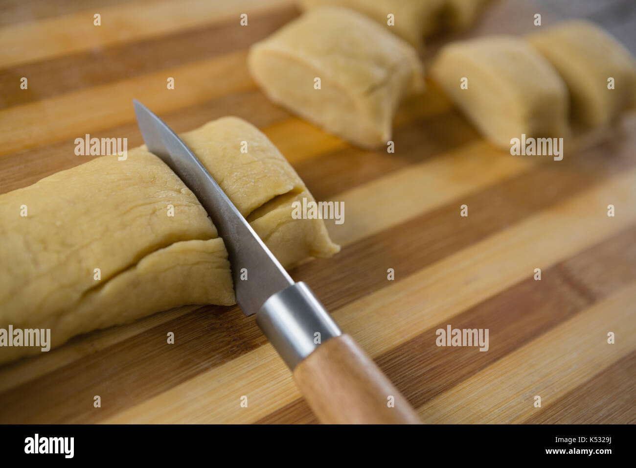 Cropped image of kitchen knife cutting dough on cutting board - Stock Image