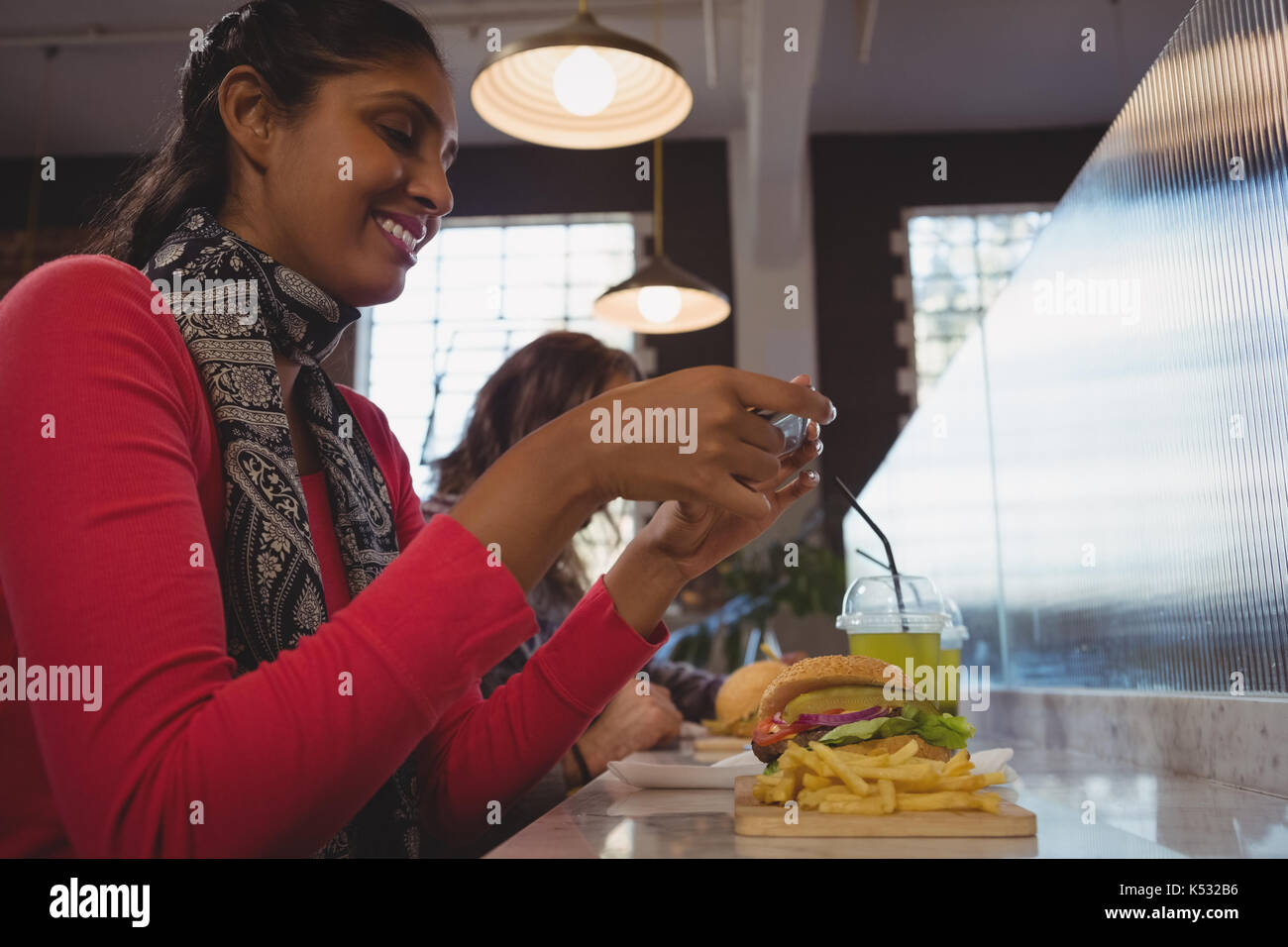 Young woman photographing French fries at counter in cafe - Stock Image