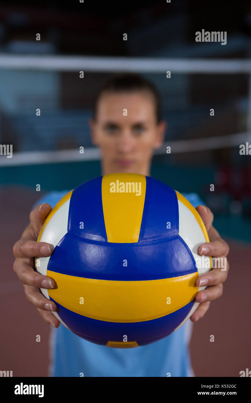 Female sportsperson holding volleyball at court - Stock Image