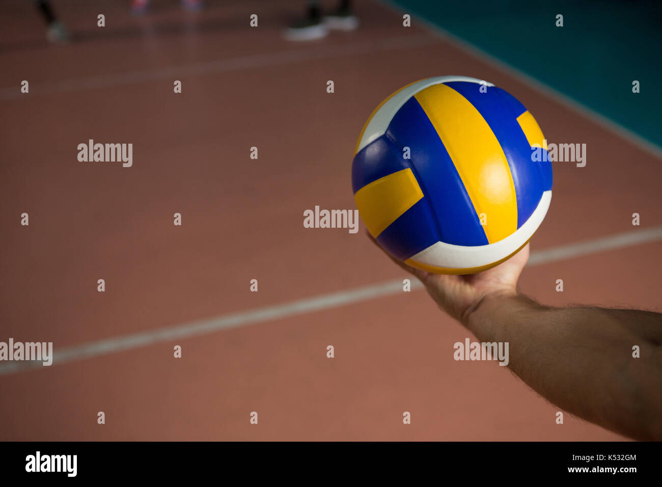 Cropped hand of sportsperson with volleyball at court - Stock Image