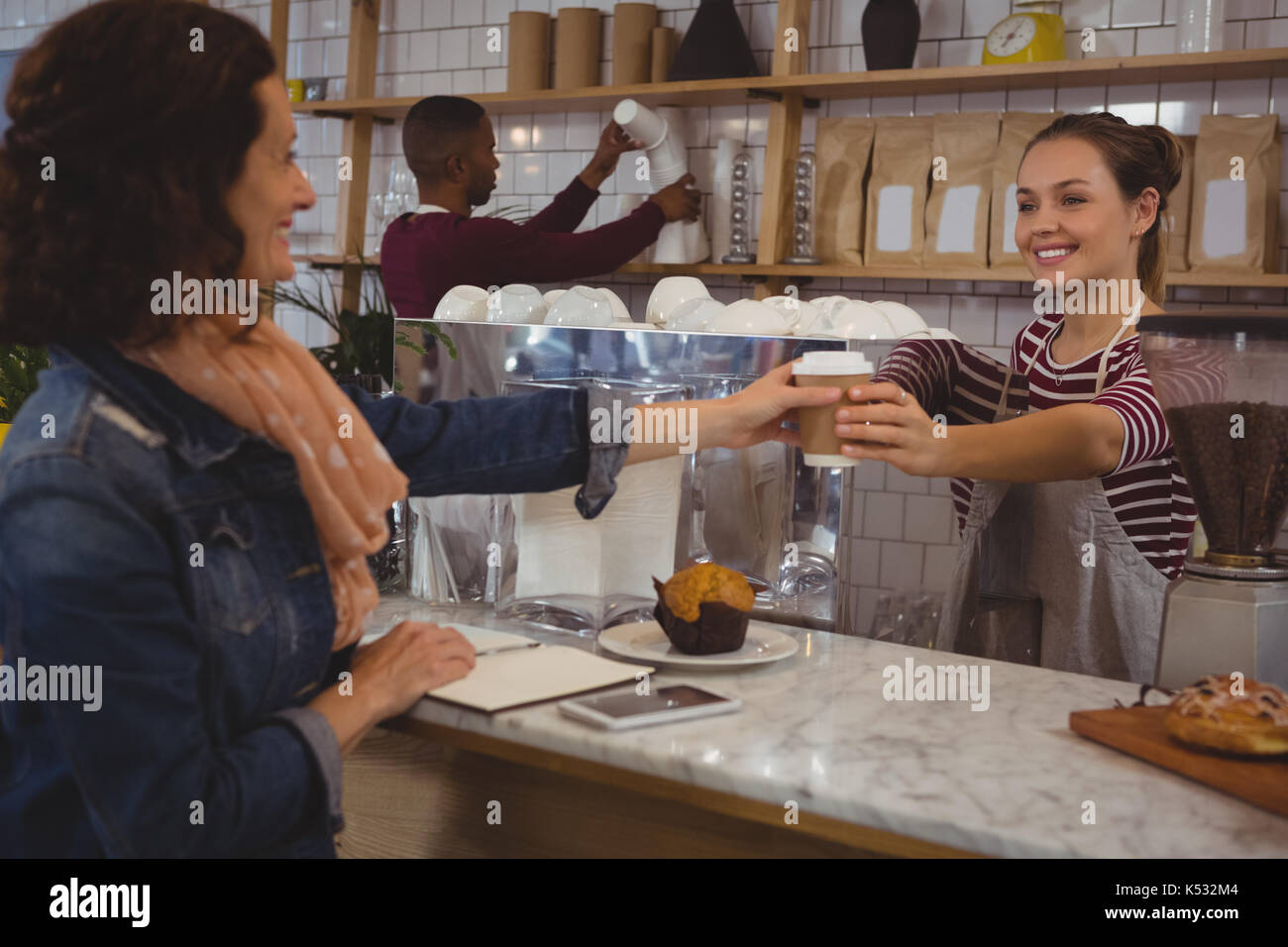 Young female owner serving coffee to customer at cafe - Stock Image