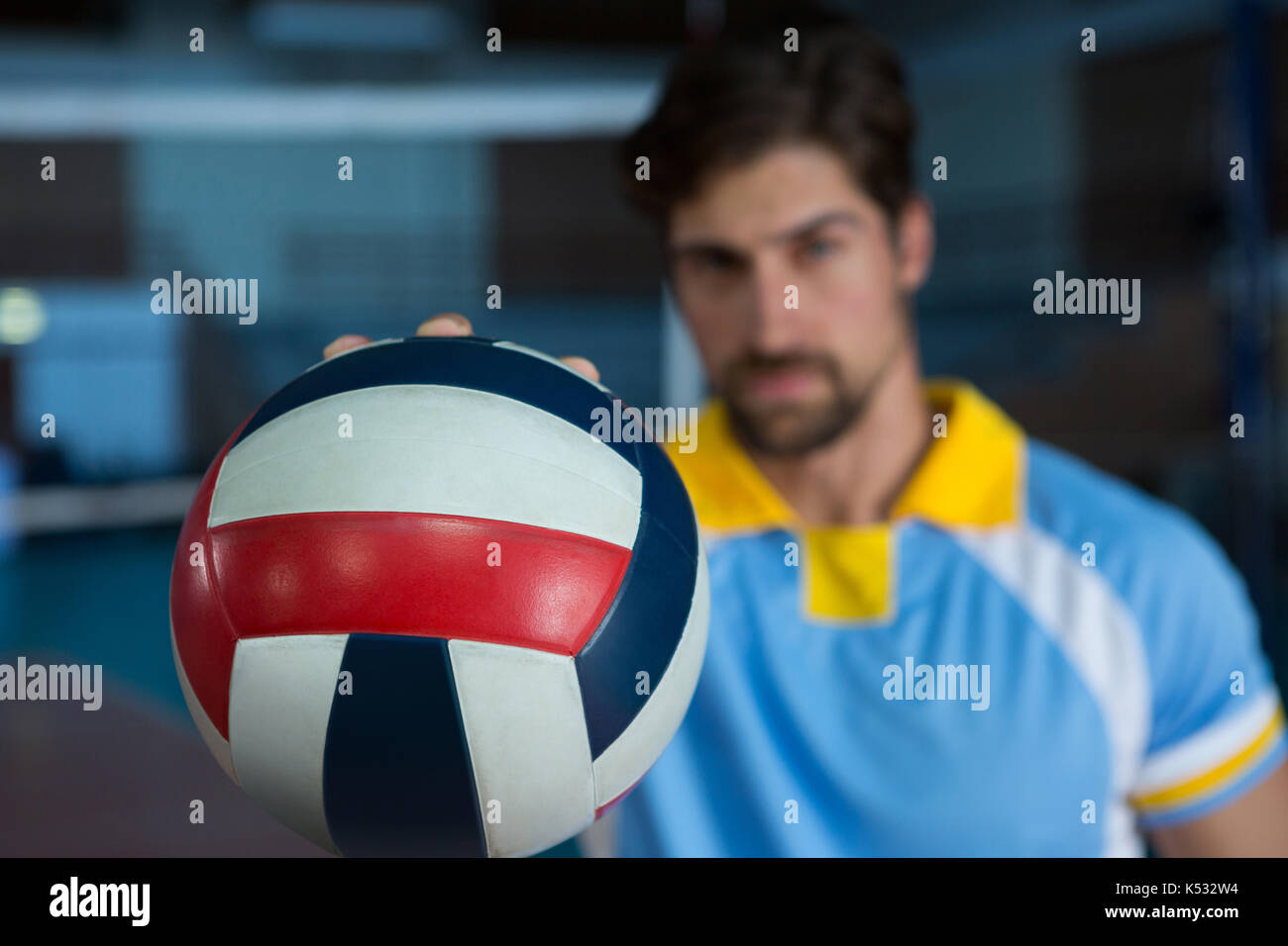 Male sportsperson holding volleyball at court - Stock Image