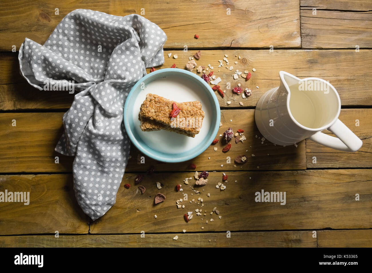 Overhead view of granola bar and milk in bowl - Stock Image