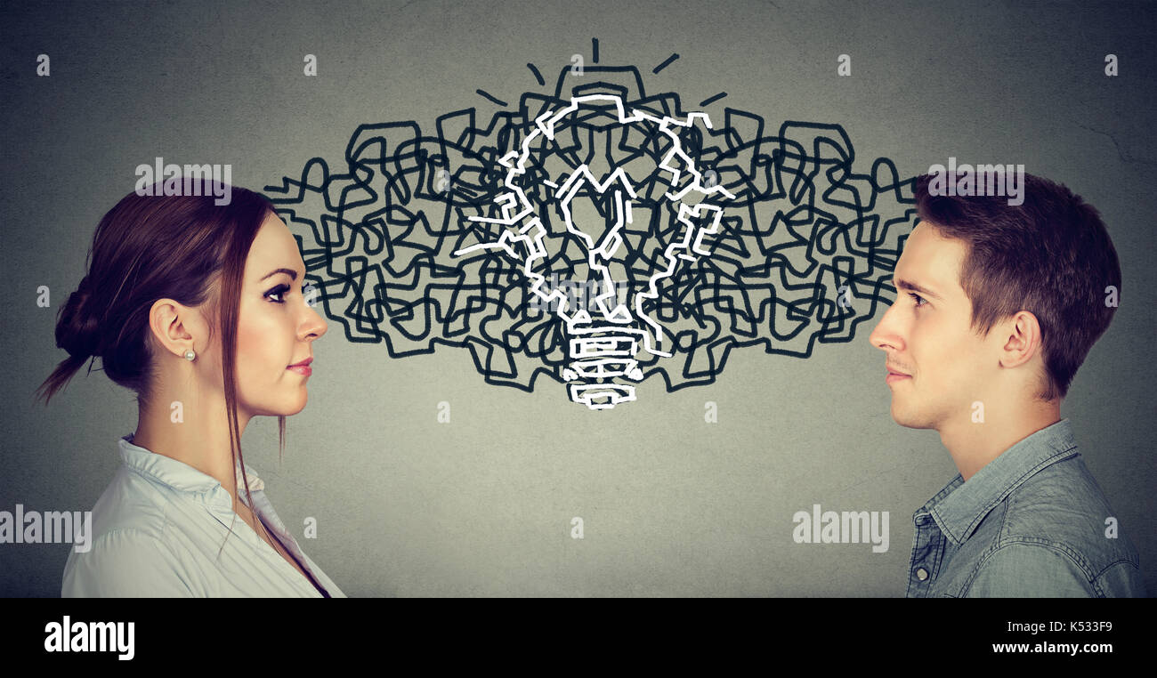 Young man and woman looking at each other exchanging their thoughts coming up together with an idea light bulb - Stock Image