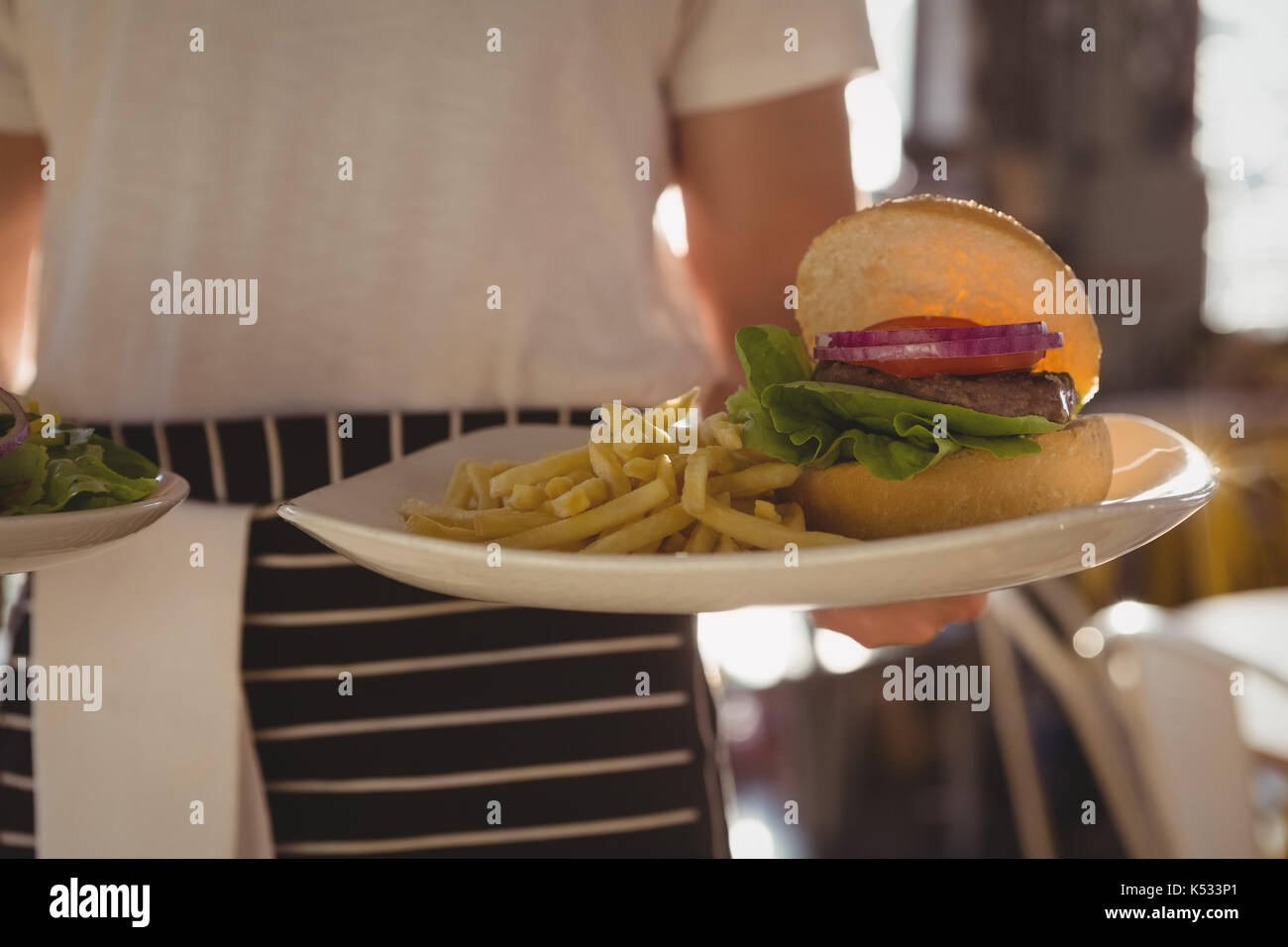 Mid section of waiter holding plate with burger and French fries at cafe - Stock Image