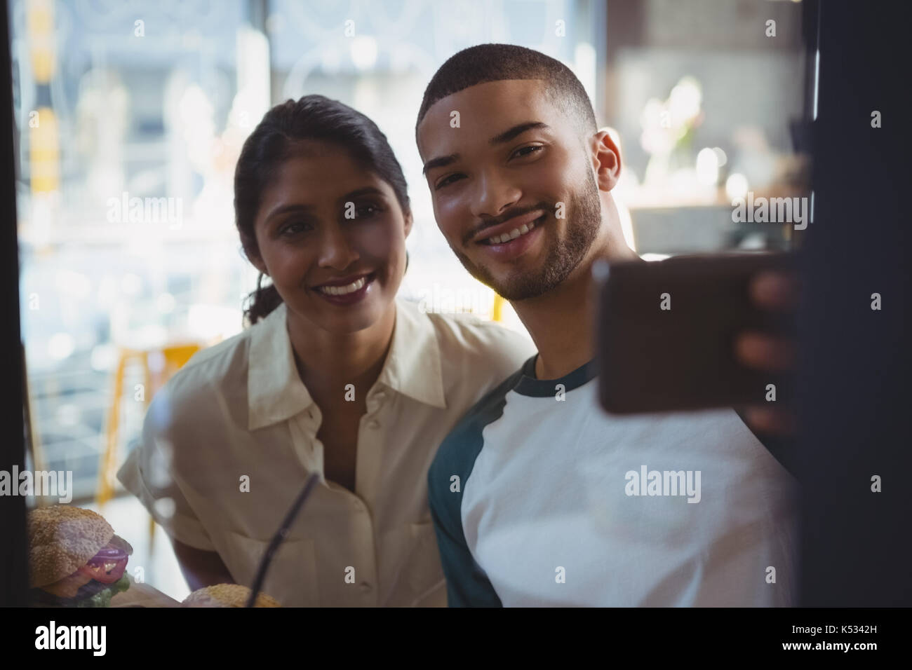 Smiling young man with woman taking selfie seen through glass in cafe - Stock Image