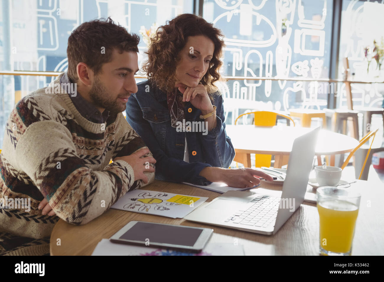 Concentrated business people using laptop at table in cafe - Stock Image