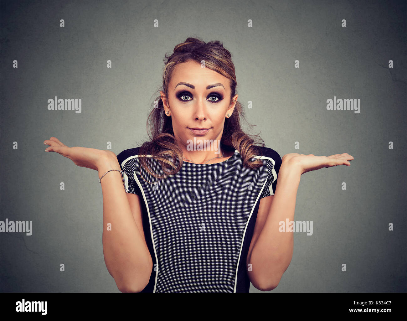 Woman has no answer shrugging shoulders looking at camera - Stock Image