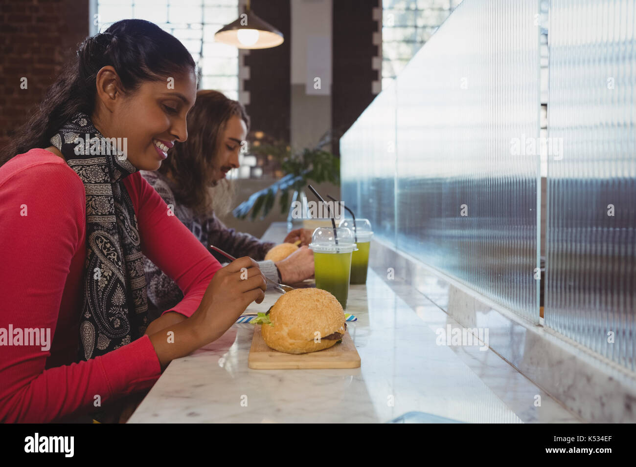 Young woman with friend having burger at counter in cafe - Stock Image