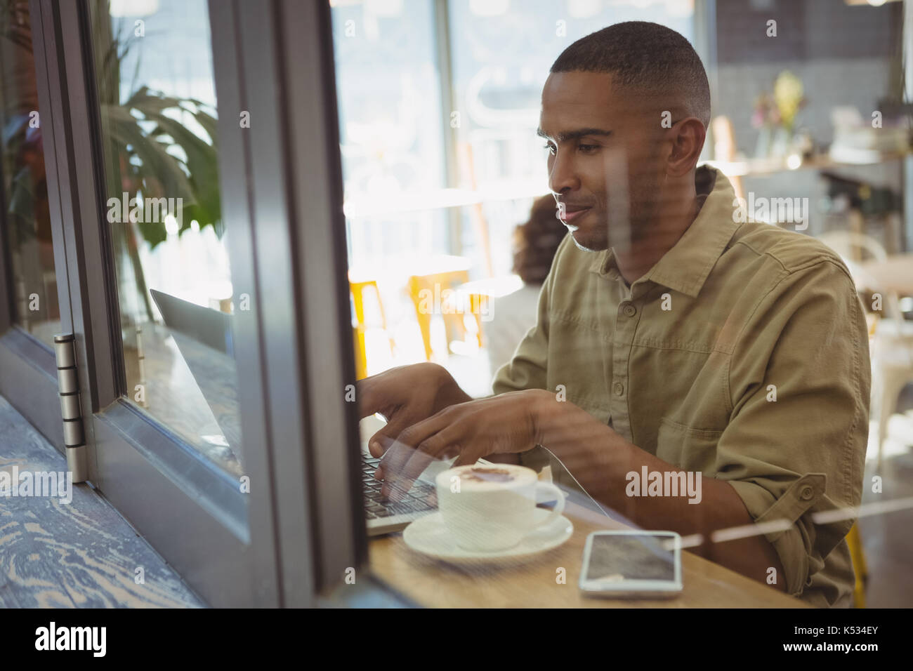 Young man using laptop seen through glass window at cafe - Stock Image