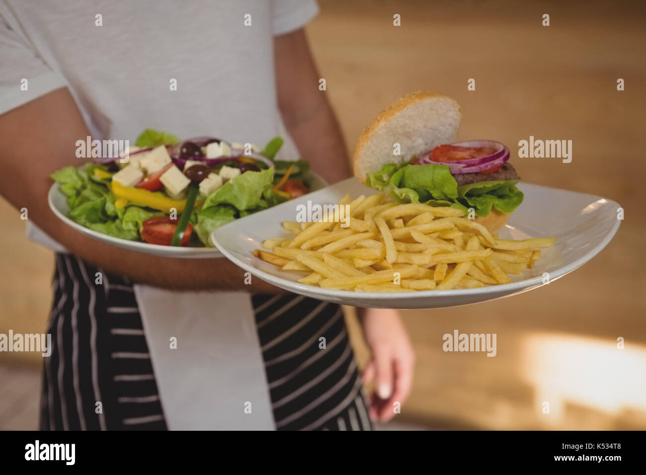Mid section of waiter holding plates with French fries and salad in cafe - Stock Image