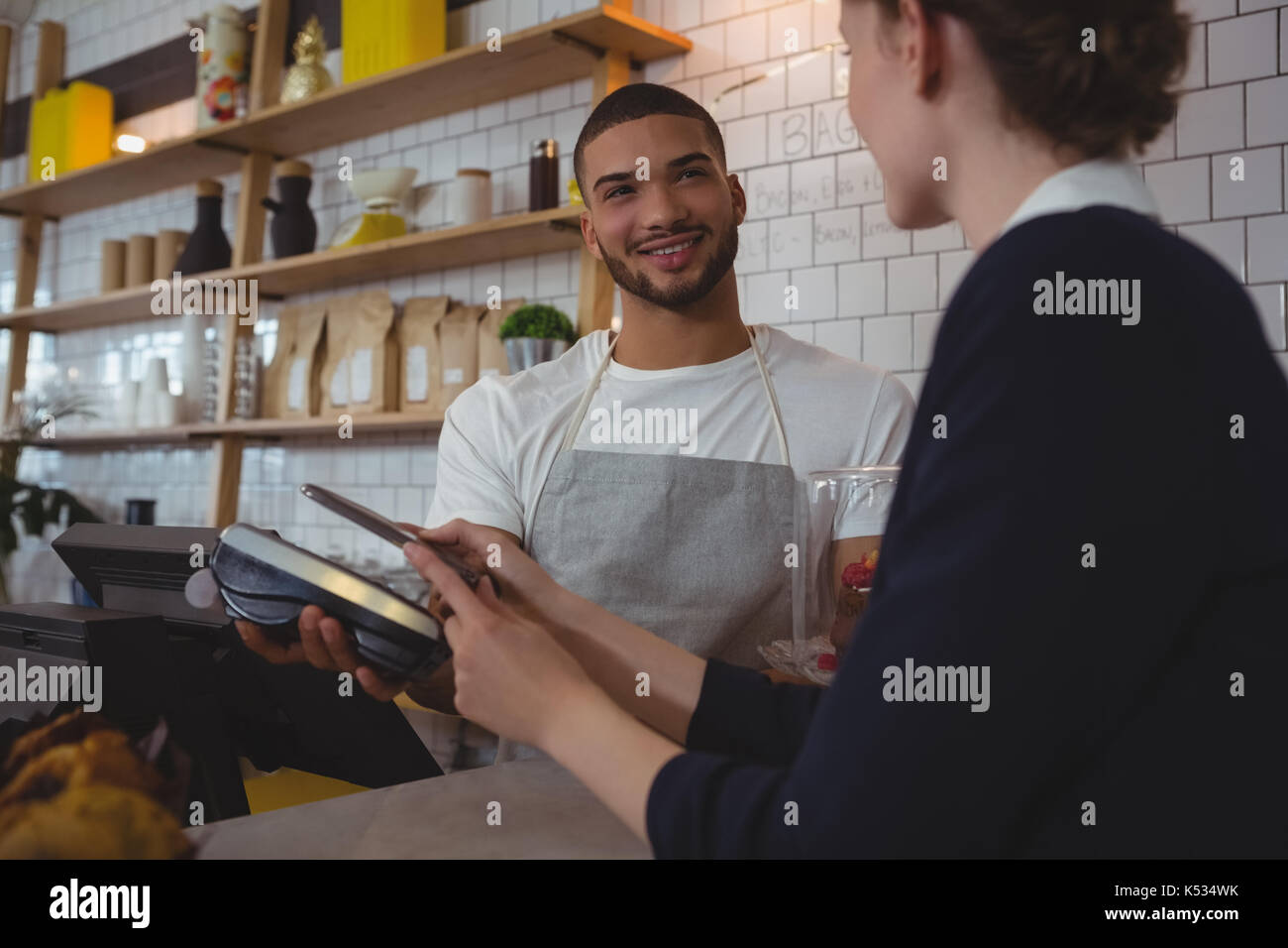 Young waiter showing credit card reader to female owner in cafe - Stock Image