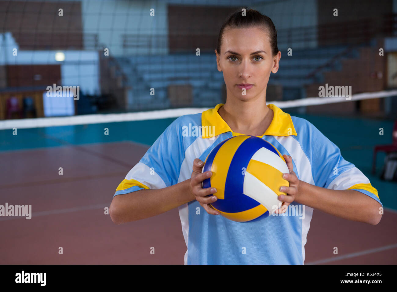 Portrait of young female sportsperson holding volleyball - Stock Image