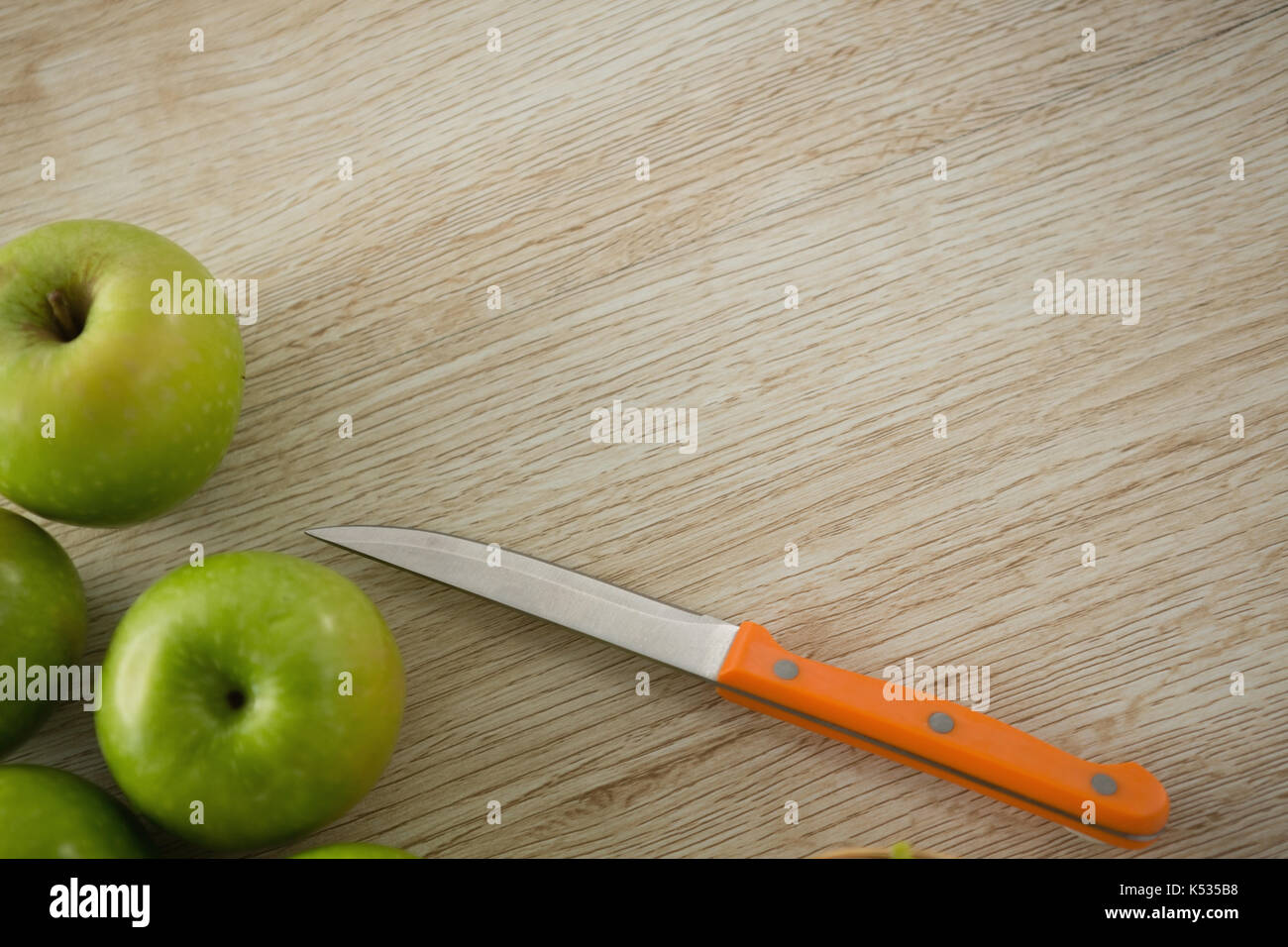 Overhead view of granny smith apple by kitchen knife on wooden table - Stock Image