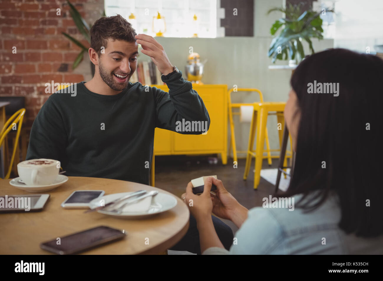 Woman giving ring to shocked young boyfriend at cafe - Stock Image