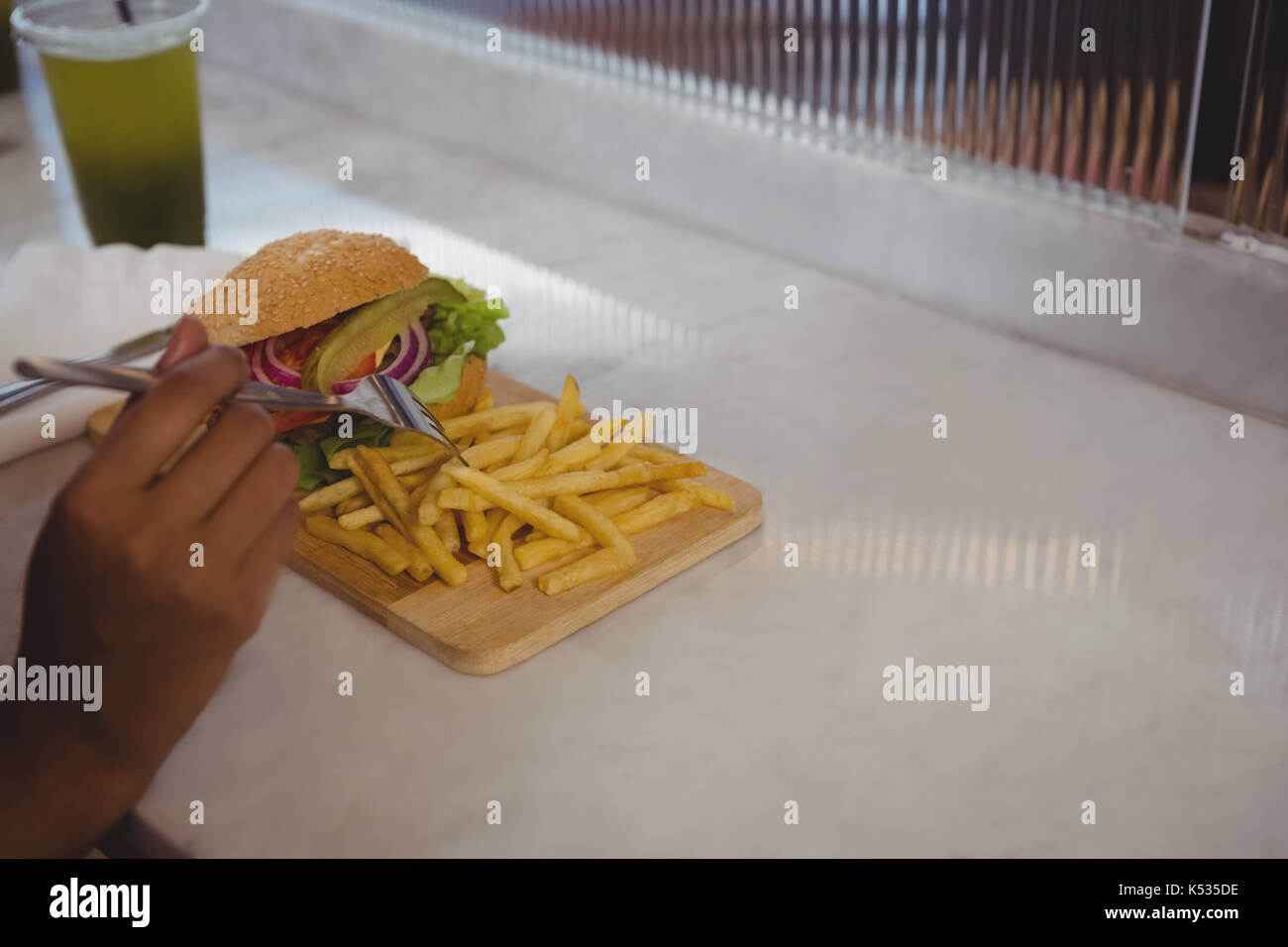 Cropped hand of woman having French fries and burger at counter in cafe - Stock Image