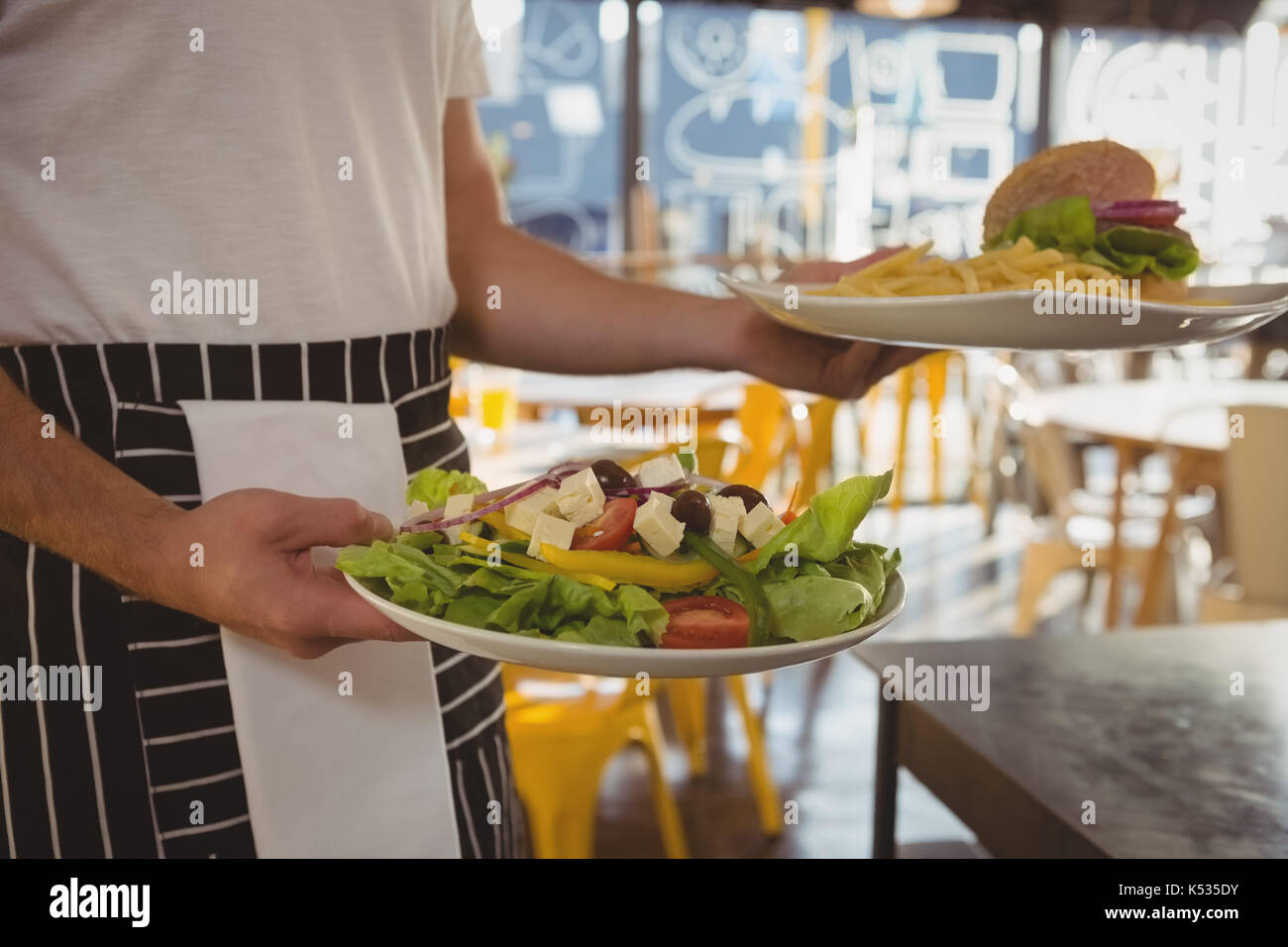 Mid section of waiter serving salad and French fries with burger in cafe - Stock Image