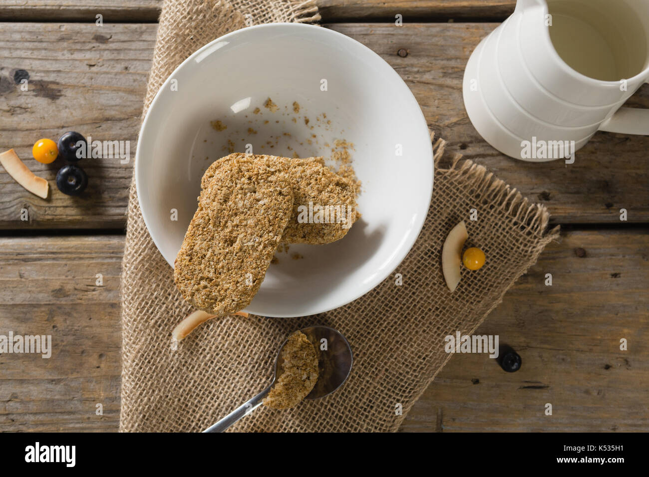 Overhead of granola bar and milk on wooden table - Stock Image