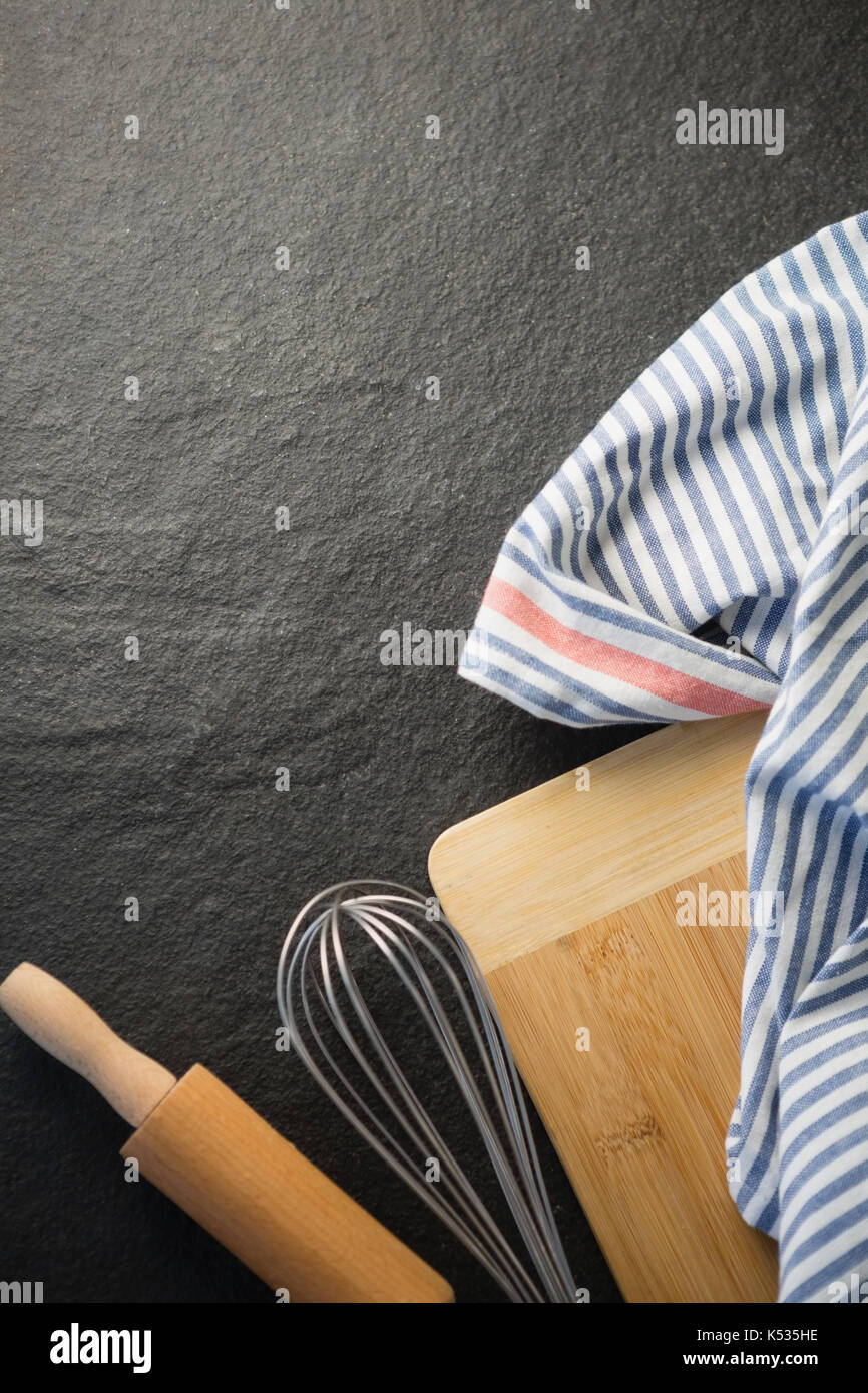 Directly above of kitchen utensils with napkin on table - Stock Image