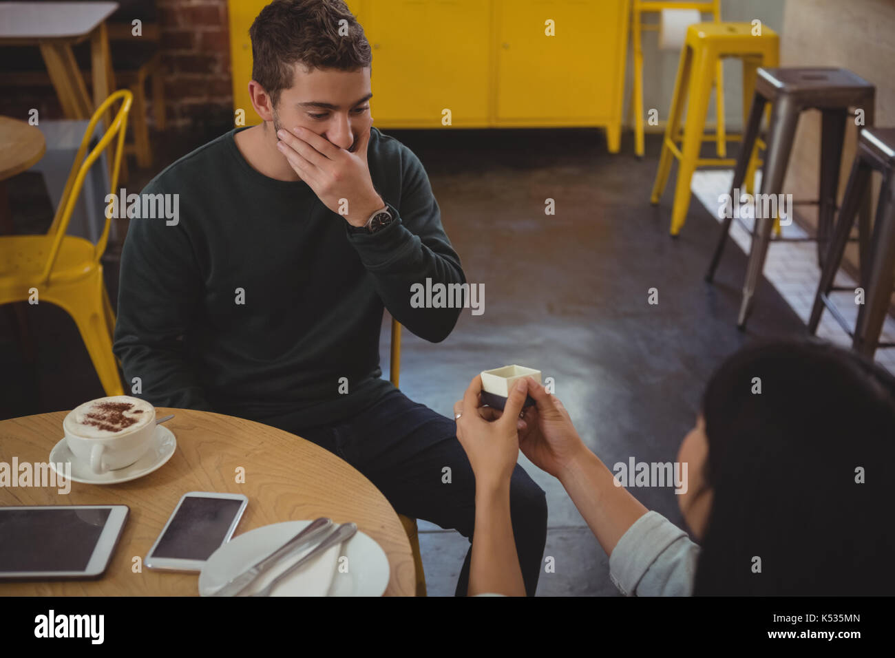 Woman gifting ring to shocked young boyfriend at cafe - Stock Image